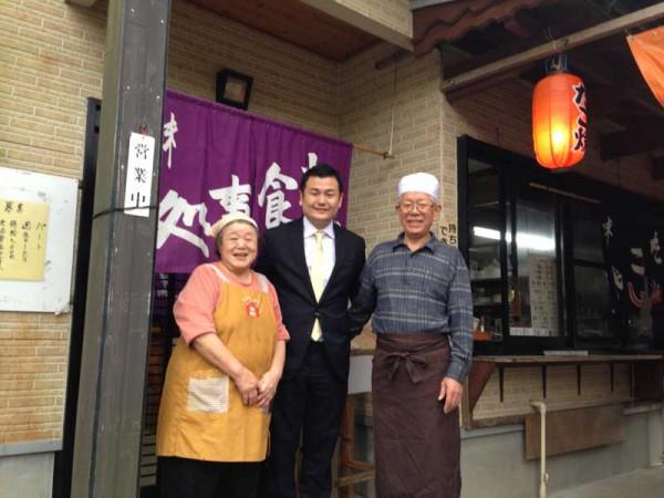 福山ご夫妻とお食事処「たこ福」の前で記念撮影する かわの義博