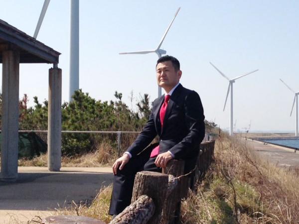 北九州市の響灘風力発電施設を背景に かわの義博